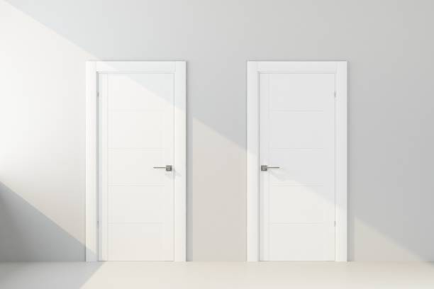 two white door in white wall stock photo