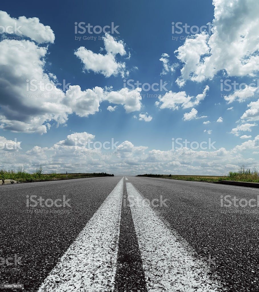 two white lines on road and dramatic sky over it stock photo