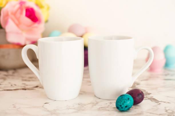 zwei weiße tassen mockup - ostern-thema. ostereier. bunte eier in matten farben. hellen marmor hintergrund - rosa zitate stock-fotos und bilder