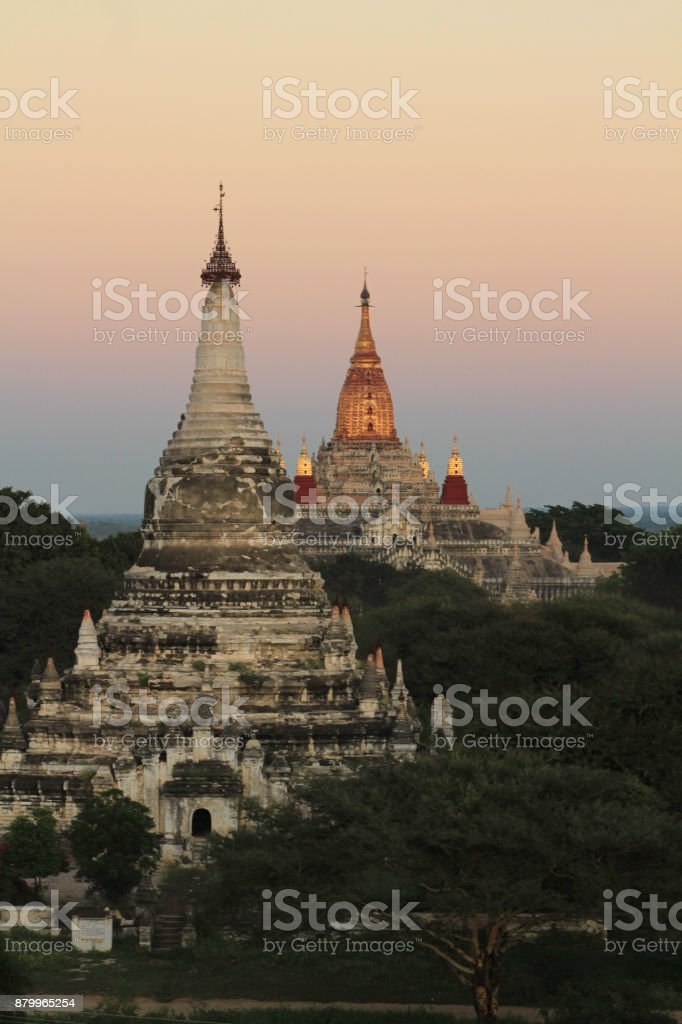 Two White Pagodas Stand Out in Sunset Among Fields of Bright Green Foliage adn Trees. Taken at Bagan, Myanmar stock photo