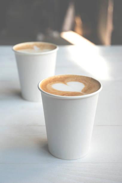Zwei weiße Papier Tassen Kaffee auf Holztisch. – Foto
