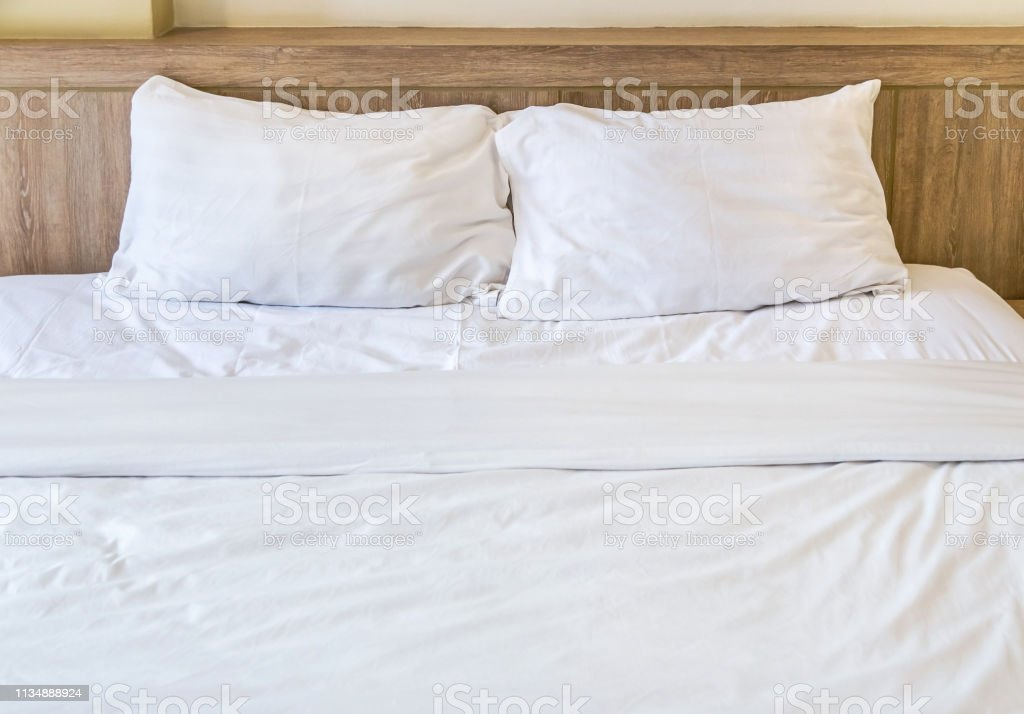 Two white pillows with white bedding sheet on empty bed in bedroom...