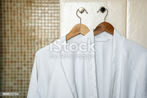 Two white rag bathrobes towels on wooden hangers in the interior of a stylish bathroom. Rest in otlele for two.