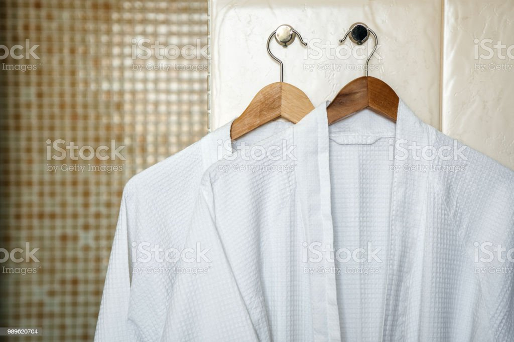 Two white rag bathrobes towels on wooden hangers in the interior of a stylish bathroom. Relax in the hotel for two. - foto stock