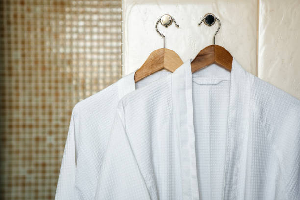 two white rag bathrobes towels on wooden hangers in the interior of a stylish bathroom. relax in the hotel for two. - accappatoio foto e immagini stock