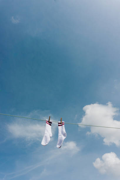 Two White Socks With Two Violet Stripes Hanging In the Sun Against Blue Sky With some Clouds stock photo