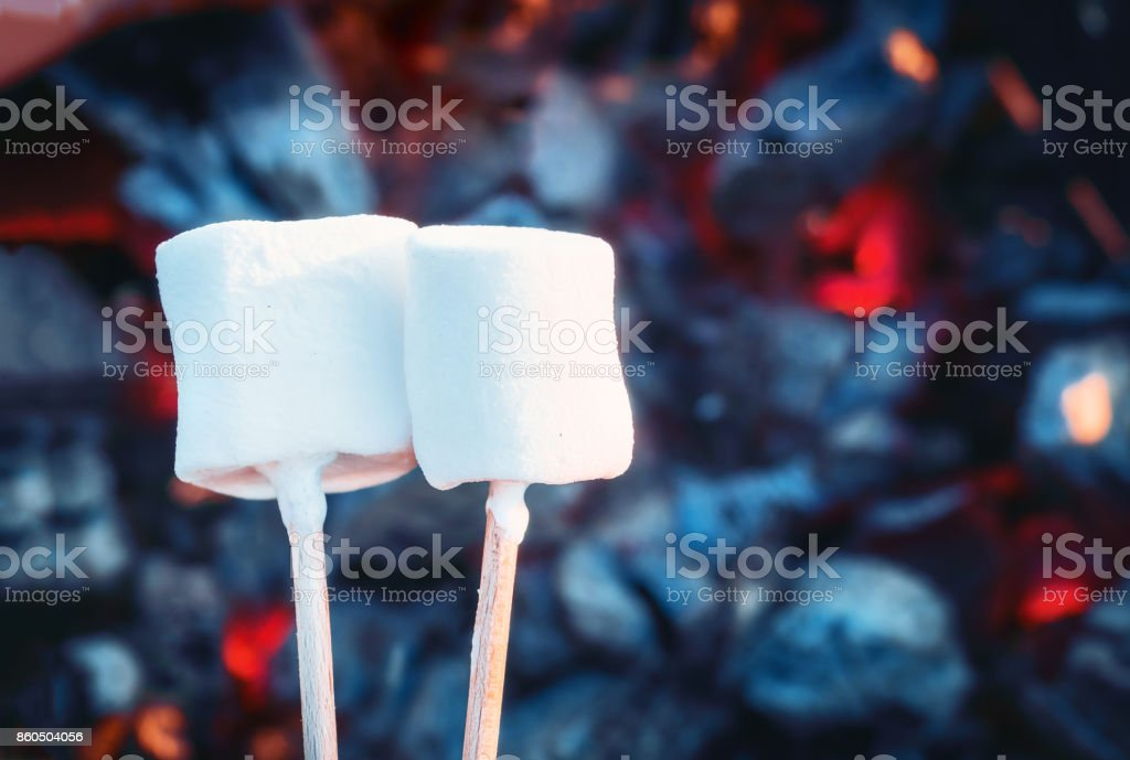 two white sweet marshmallows roasting over fire flames marshmallow
