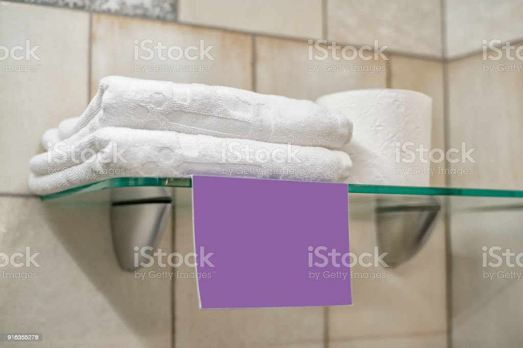 Two white towels, a roll of toilet paper and a blank lilac label on...