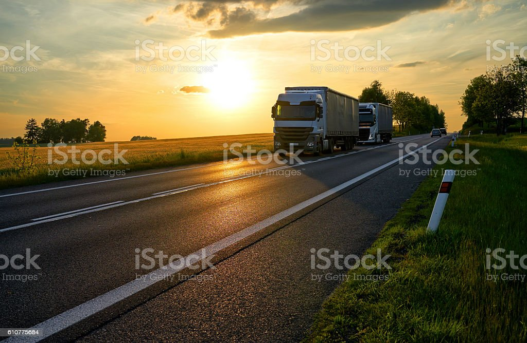 Two white trucks driving on the road at sunset. stock photo