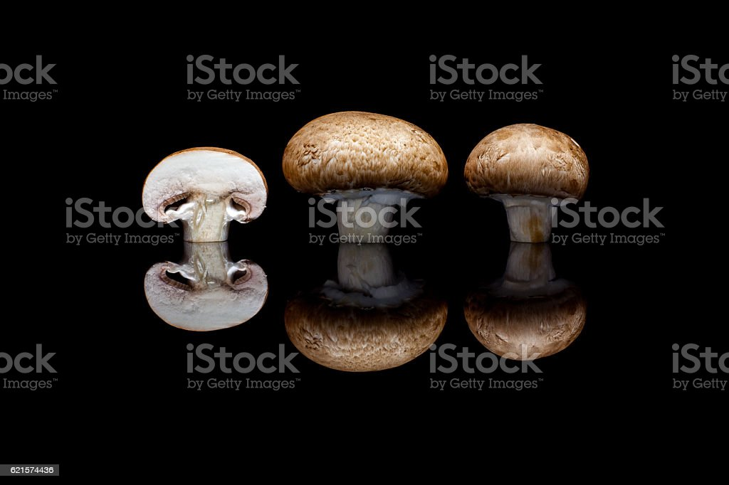 Two whole and one cut brown champignons on black background photo libre de droits