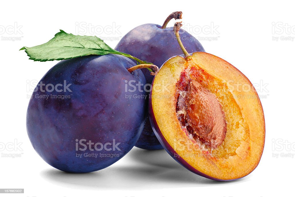 Two whole and one sliced plum with flesh and pit showing  stock photo