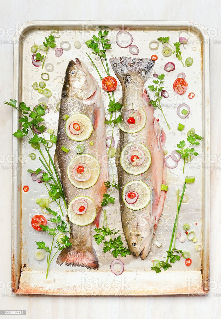 Two whole fish with ingredients on baking pan, top view stock photo