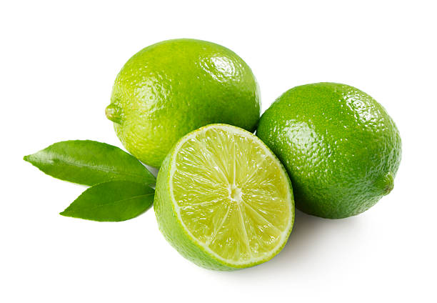 Two whole limes and one halved lime with leaves stock photo