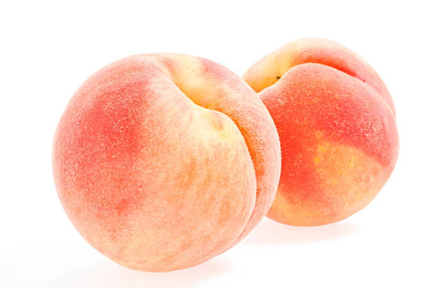 Two whole peaches on a white background stock photo