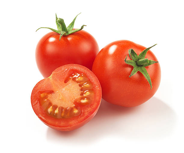 Two whole red ripe tomatoes and one in half stock photo