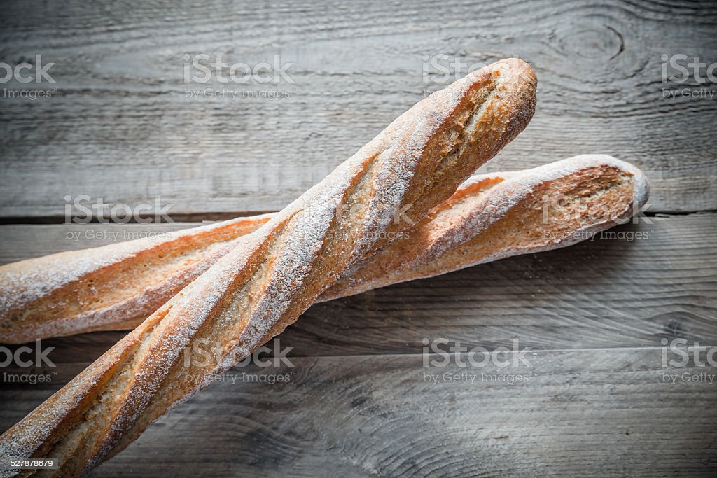 Two wholewheat baguettes on the wooden background stock photo