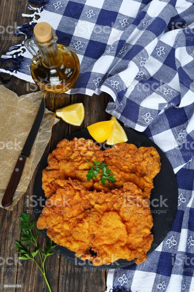 two Wiener schnitzel on black stone plate stock photo