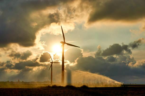 日落時兩颱風力渦輪機和灌溉農作物水槍或水噴霧 - 氣候 個照片及圖片檔
