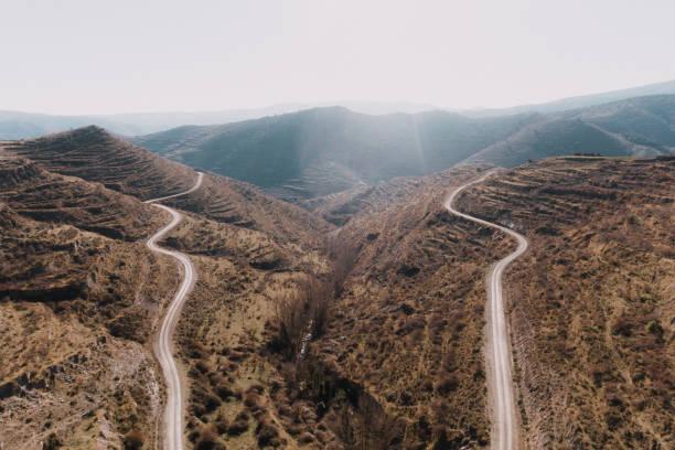 twee bochtige wegen op het gebied van de bergen - parallel stockfoto's en -beelden