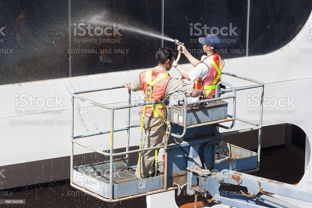 Two Window Washers cleaning Windows of a Cruise Ship stock photo