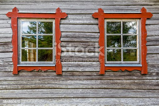 istock Two windows on log house wall, traditional style. 584860970