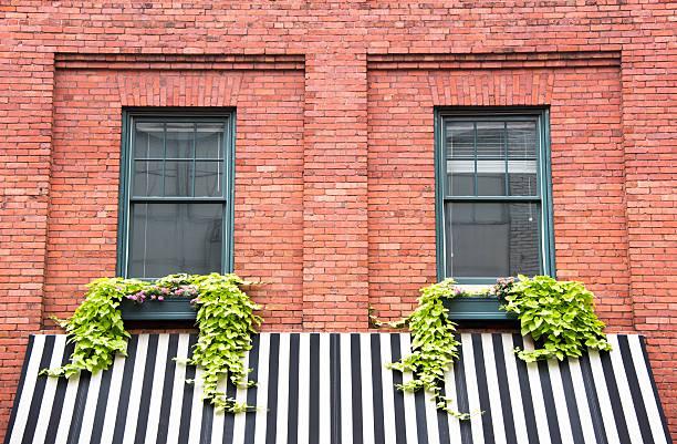 two windows over striped awning - horizontal gestreiften vorhängen stock-fotos und bilder