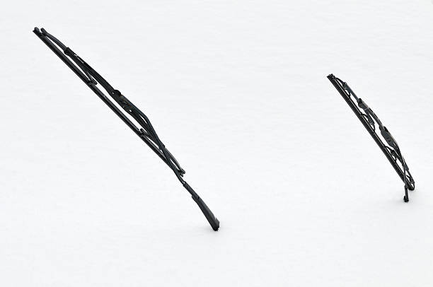Two windscreen wipers poking out of a blanket of snow First snow on a car windshield wiper stock pictures, royalty-free photos & images