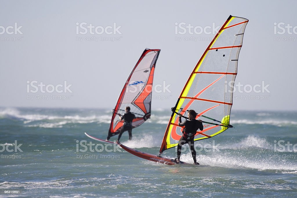 Two windsurfers on the water in wetsuits royalty-free stock photo