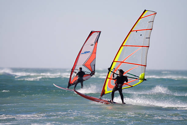 Two windsurfers on the water in wetsuits stock photo