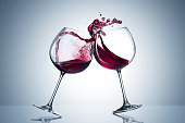 Two wine glasses in toasting gesture with big splashing. Alcohol concept. Two glasses of wine on the gray background. Two transparent glasses. Trendy color. Merging alcohol