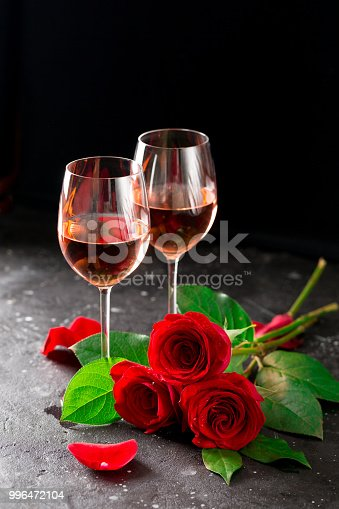 Two wine glasses of rose wine on dark background, bouquet of red roses petals against brown brick wall romantic evening for Valentines day surprise intimate set up love affair celebration copy space