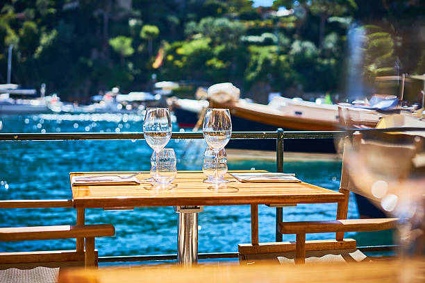 two wine glasses on table at harbor - französische land tisch stock-fotos und bilder