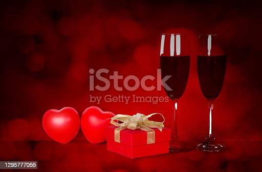 Two wineglasses and red gift box and heart shape on desk with red blur bokeh background, champagne glasses and presents with celebration and anniversary, love and romantic, valentine day concept.