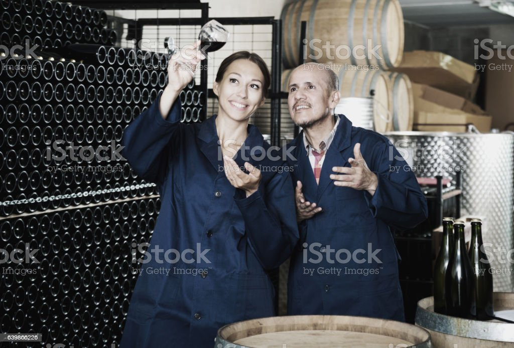 Two winery workers holding glass of wine stock photo