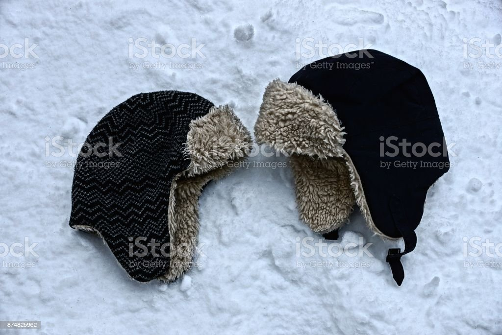two winter hats in the snow on the street stock photo