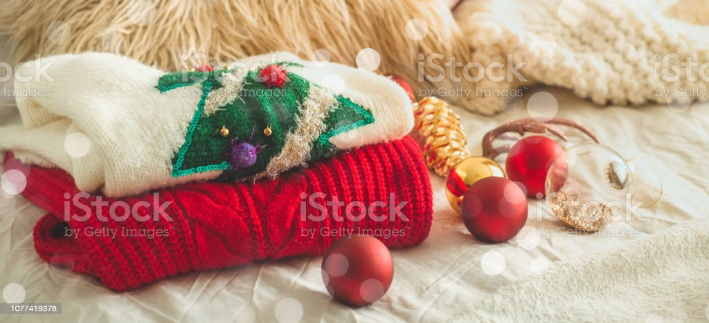 Two winter sweaters laid on a bed with pillows and New Year's decorations stock photo