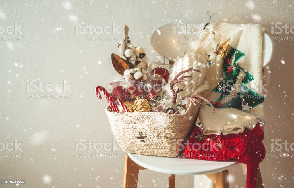 Two winter sweaters laid on a chair with a basket of Christmas decorations and led string lights. Winter mood, holiday decoration. stock photo