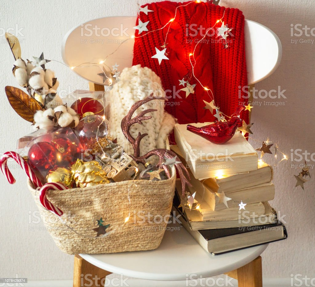 Two winter sweaters laid on a chair with a basket of Christmas decorations, books, led string lights. Winter reading. Winter mood stock photo
