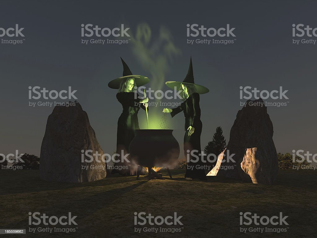 Two witches brewing up a green potion in cauldron stock photo