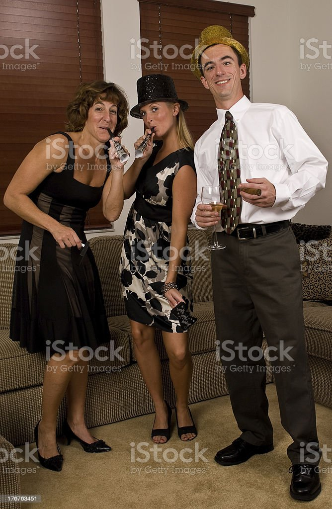 Two woman and a man celebrating New Years stock photo