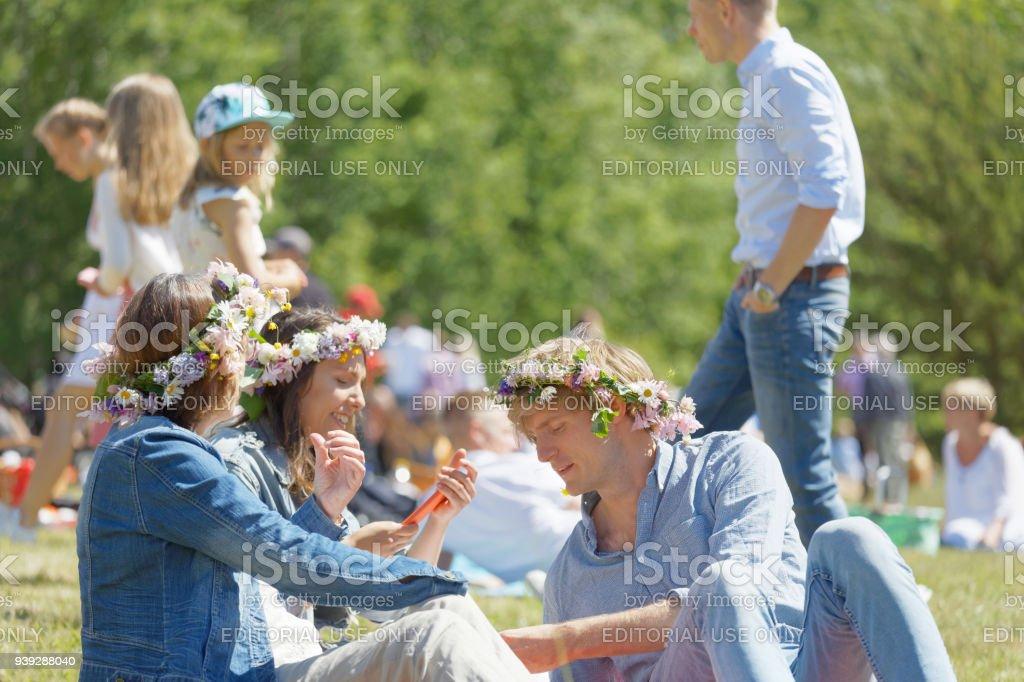 İki kadın ve bir adam bir piknik İsveç'te Midsummer kutlama önce otların arasında oturan sahip onların saç çiçekli stok fotoğrafı