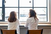 カフェで窓のそばでおしゃべりしている2人の女性
