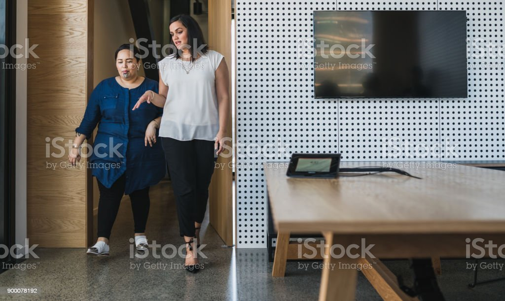 Two woman entering in meeting room. stock photo