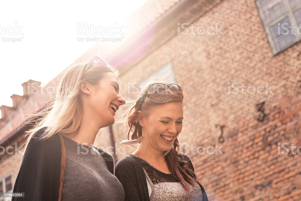 Two woman friends walking in the city enjoying their time stock photo