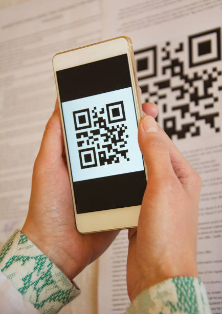 Two woman hands scanning QR code using smart phone stock photo
