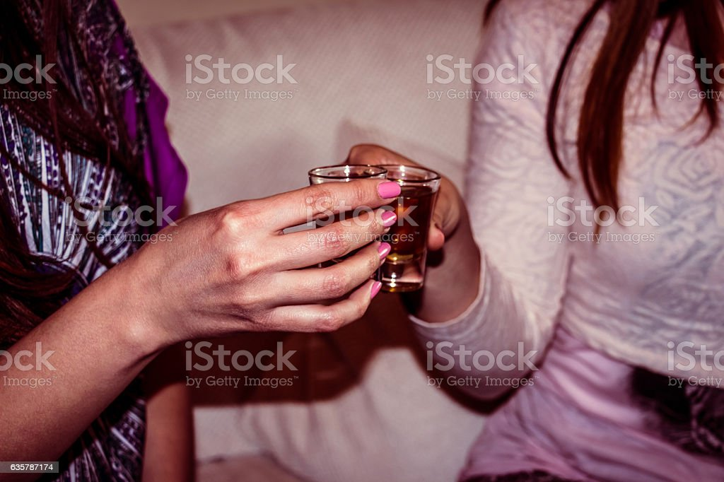 Two woman hands toasting whiskey stock photo