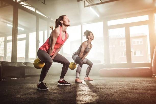 dos mujeres levantando la campana de la tetera en el gimnasio cross fit - pesa rusa fotografías e imágenes de stock