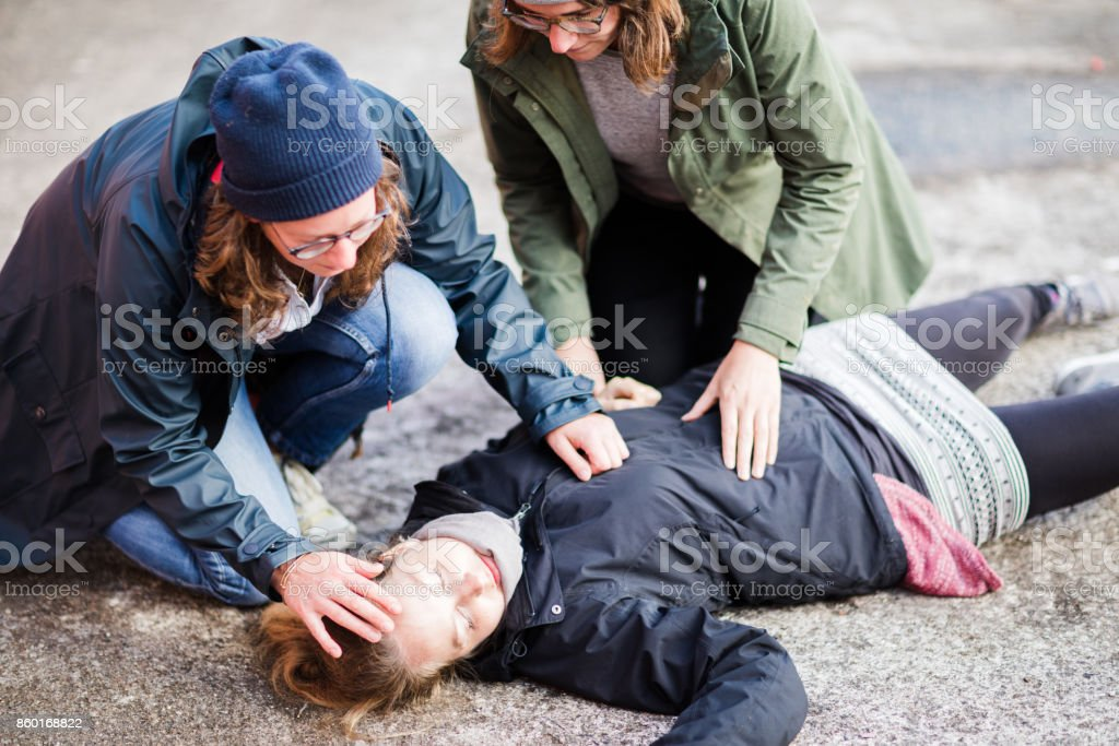 Two woman looking after unconscious woman stock photo