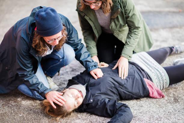 Duas mulher cuidando de mulher inconsciente - foto de acervo