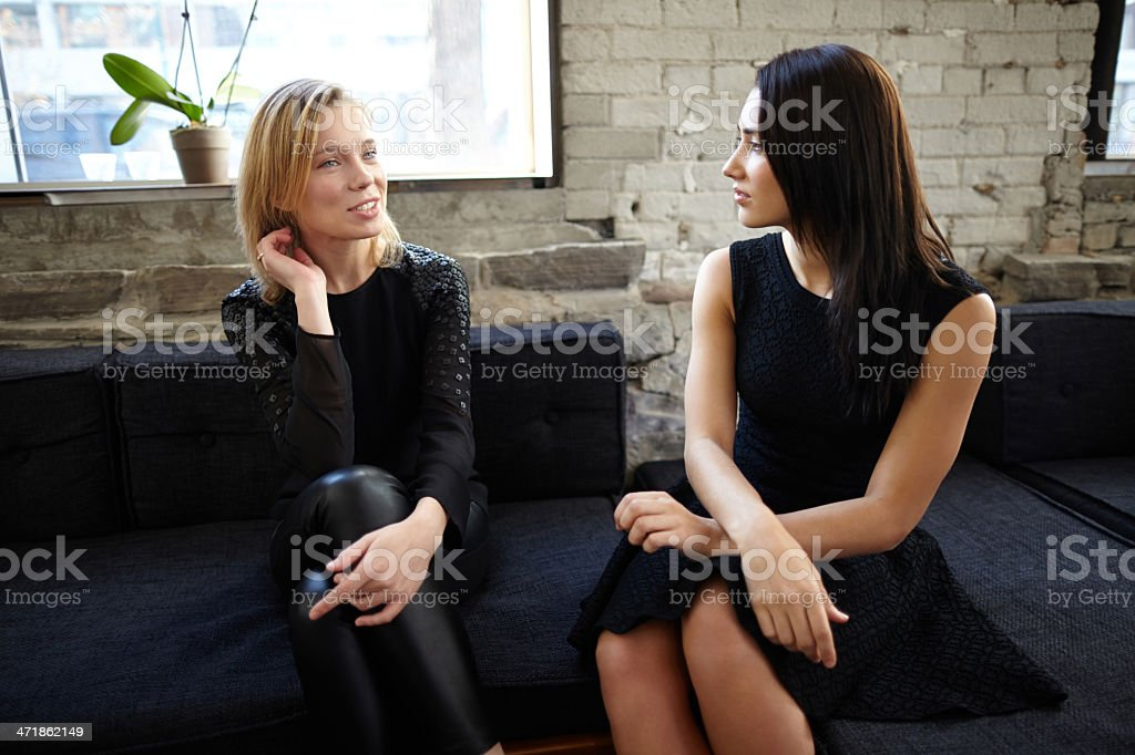 Two woman sitting on restaurant sofa chatting royalty-free stock photo